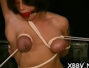 Bare wife stands booked up and endures heavy breast bondage